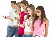 Row Of Five Friends Using Cellular Phones Smiling