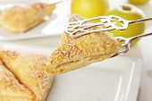 Pastry tongs taking apple turnover from a platter