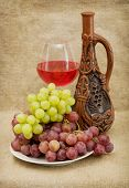 picture of loamy  - Ceramic brown bottle grapes and red wine on canvas - JPG