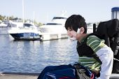 image of biracial  - Disabled biracial six year old boy pushing himself in wheelchair on lake pier - JPG