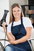 Environmental portrait of confident female hairdresser holding hairdryer at salon