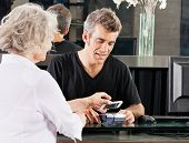 stock photo of over counter  - Hairdresser with female client paying with mobilephone over electronic reader at counter - JPG