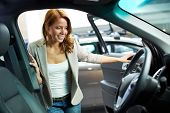 Photo of elegant woman choosing a new car in automobile center