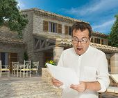 Horrified man reading a document by a magnificent house