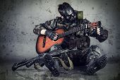 picture of war terror  - sitting man in gas mask plays guitar - JPG