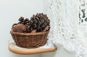Pine cones in a wicker basket standing on the wooden shelve.