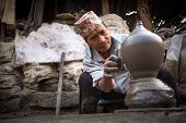 BHAKTAOUR, NEPAL - DEC 7: Unidentified Nepalese man working in his pottery workshop, Dec 7, 2013 in