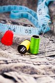 Needle, two colourful reels of cotton, a thimble and a tape measure on denim cloth for sewing, alter