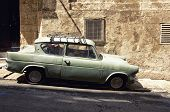 picture of brownstone  - A very old car is parked in a narrow street of Valletta the capital city of Malta - JPG