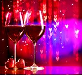 Valentine's Day Celebrating. Holiday. Two Glasses of Red Wine over Blurred Blinking Background with Hearts. Symbol of Love. Gala Dinner at the restaurant. Date
