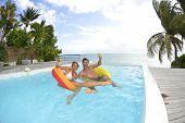picture of infinity pool  - Couple swimming in infinity pool - JPG