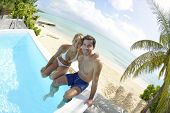 image of infinity pool  - Happy young couple sitting in infinity pool - JPG
