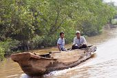 Vietnamese men ride the boat on Mekong Delta