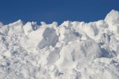 stock photo of plowing  - Large pile of plowed snow against blue sky - JPG