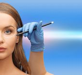 health, beauty and plastic surgery concept - woman face and beautician hands with pencil