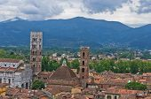 Cityscape of Lucca with cathedral and surrounding mountains, Tuscany