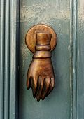 Bronze door handle in form of a hand