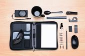 High angle shot of all black assorted desk items. Items include: mug, stapler, pencil, pen, eraser,