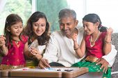 stock photo of sari  - Asian Indian family playing carrom game at home - JPG