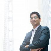 Portrait of a good looking smiling Indian businessman crossed arms standing at modern building, with