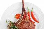 meat food : grilled beef spare rib on white dish with thyme pepper and tomato isolated over white ba