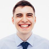 Film toned grainy portrait of laughing young employee