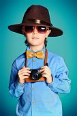 Portrait of a cute 7 year old boy in elegant hat and bow-tie making photographs by his camera. Occup