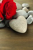 Grey stone in shape of heart, on wooden background