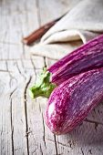two fresh eggplants on an old wooden board