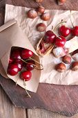 Tasty homemade strudel and fresh sweet cherry on paper napkin, on wooden table background