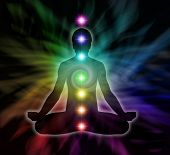 stock photo of chakra  - Silouette of a man in lotus meditation position with Seven Chakras on flowing rainbow energy background - JPG