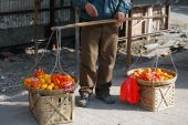 pic of yoke  - street vendor selling and carrying oranges in yoked baskets - JPG