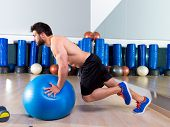 Fitball abdominal push ups Swiss ball man one single leg pushup at fitness gym