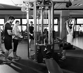 stock photo of pulley  - cable pulley system gym workout fitness people with personal trainer - JPG