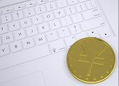 Gold yen coin on the keyboard
