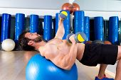 Dumbbell chest press on fit ball man workout at fitness gym