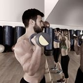 Dumbbell weightlifting man and women workout group at gym looking at mirror