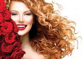 Beauty woman with long curly red hair and beautiful red roses hairstyle. Fashion model girl with blowing healthy wavy hair isolated on white background. Glamour lady portrait with red roses bouquet