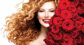 Beauty model girl with long curly red hair and beautiful red roses hairstyle. Fashion woman with blo