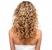 Beauty girl with blonde curly hair. Healthy and long Blond Wavy hair. Long permed hair. Beautiful yo