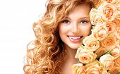 Beauty teenage model girl with curly long hair and bouquet of beautiful roses. Blonde young woman portrait closeup. Isolated on white background. Holiday Hairstyle and makeup