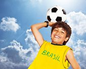 Boy playing football outdoor, happy child, teen goalkeeper enjoying sport game, holding ball, portra