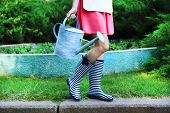Young woman in rubber boots holding watering can, outdoors