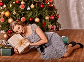 Happy woman receiving gifts under Christmas tree.