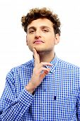Young casual man touching his chin over white background