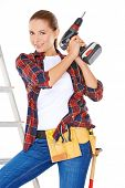 Competent attractive young DIY woman balancing on a stepladder holder a drill and wearing a tool belt  over white