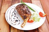 meat over wood: grilled shoulder on plate with tomatoes green lettuce on white plate