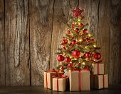 Decorated Christmas tree and gifts on wooden  background