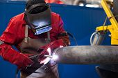 stock photo of pipe-welding  - welder in factory with protective equipment welding metal pipes - JPG