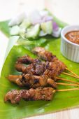 Tasty chicken sate or satay, skewered and grilled meat, served with peanut sauce. Fresh cooked with steamed and smoke. Hot and spicy Asian dish.